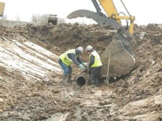 UXO Technicians inspect and prepare for removal of contaminated pipe.