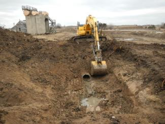 Excavation of soil for pipe inspection, with one of several former ammunition plant structures in background